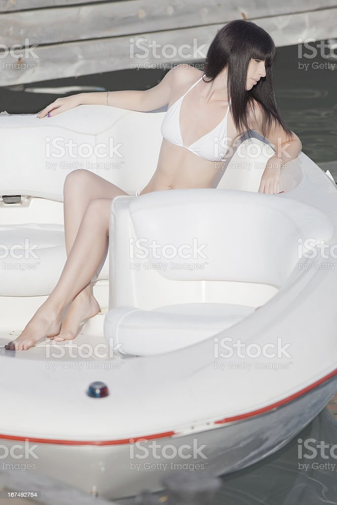 Attractive young woman in white recreational boat royalty-free stock photo