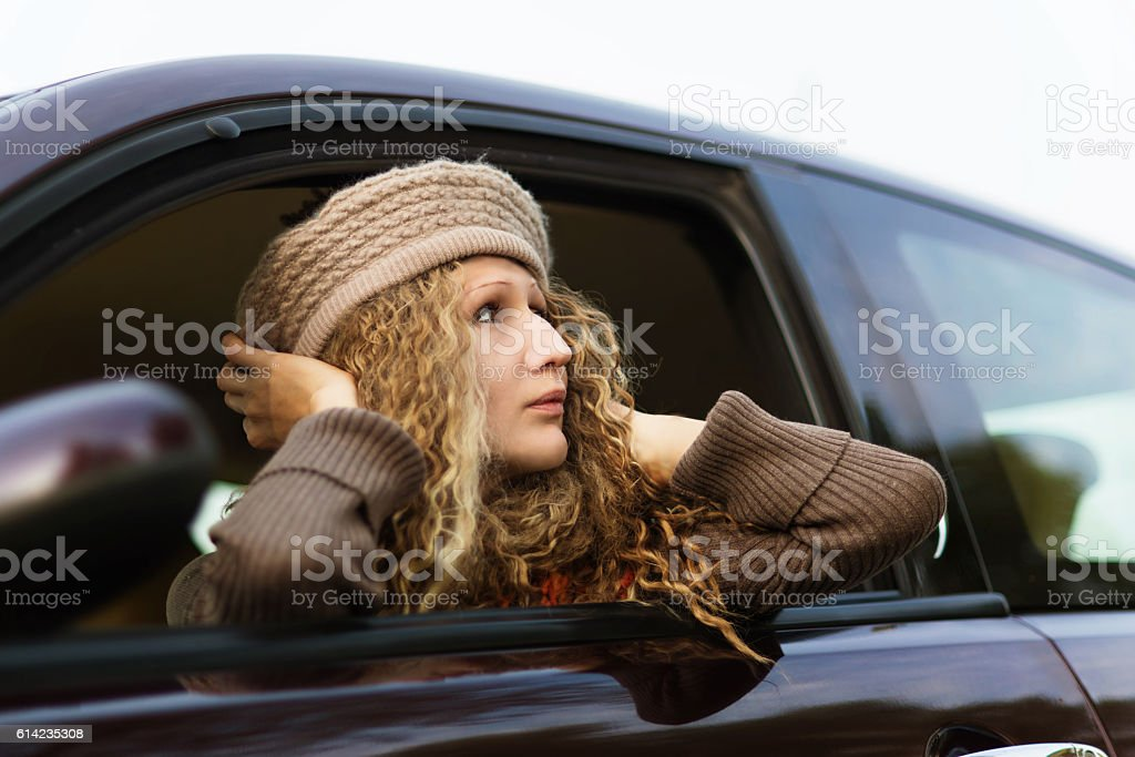 Attractive young woman into the purpil car stock photo