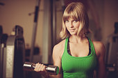 attractive young woman is engaged in sport club working out