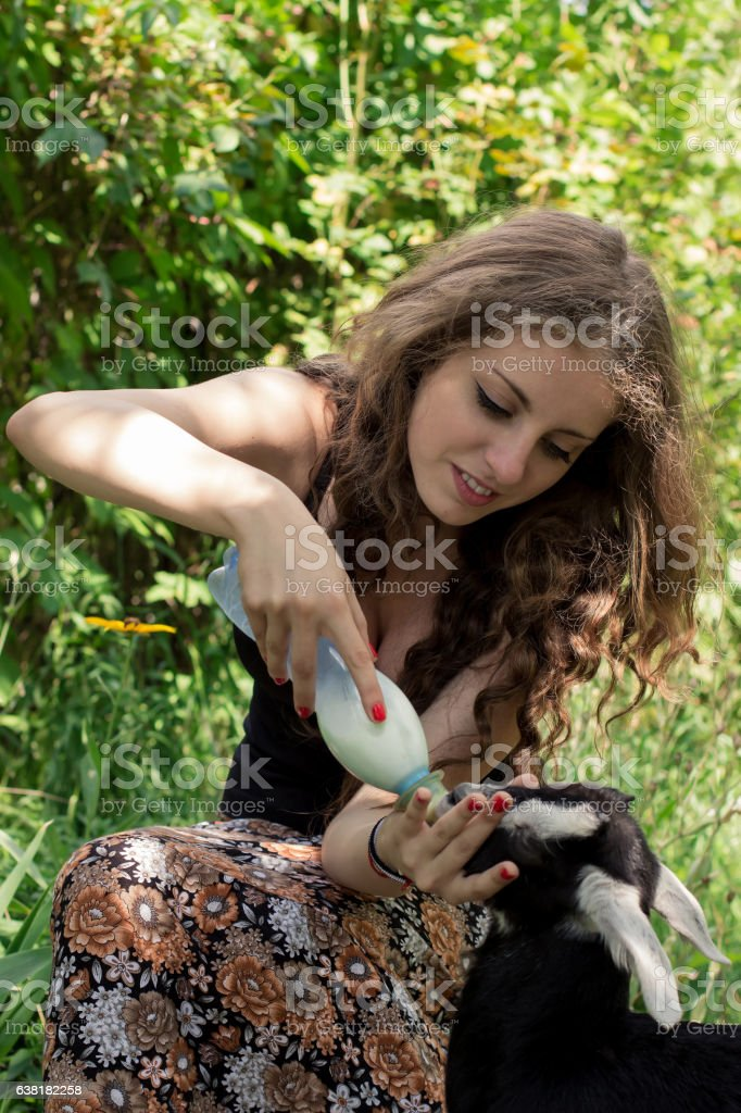 Attractive young woman is feeding a baby goat with milk stock photo