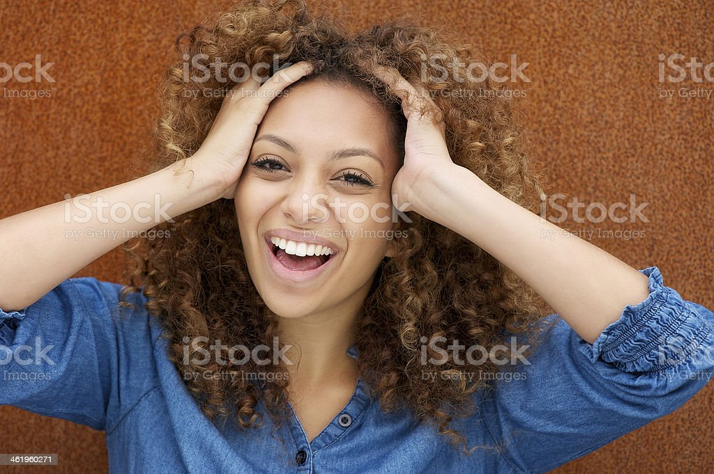 Attractive young woman laughing with hands in hair stock photo