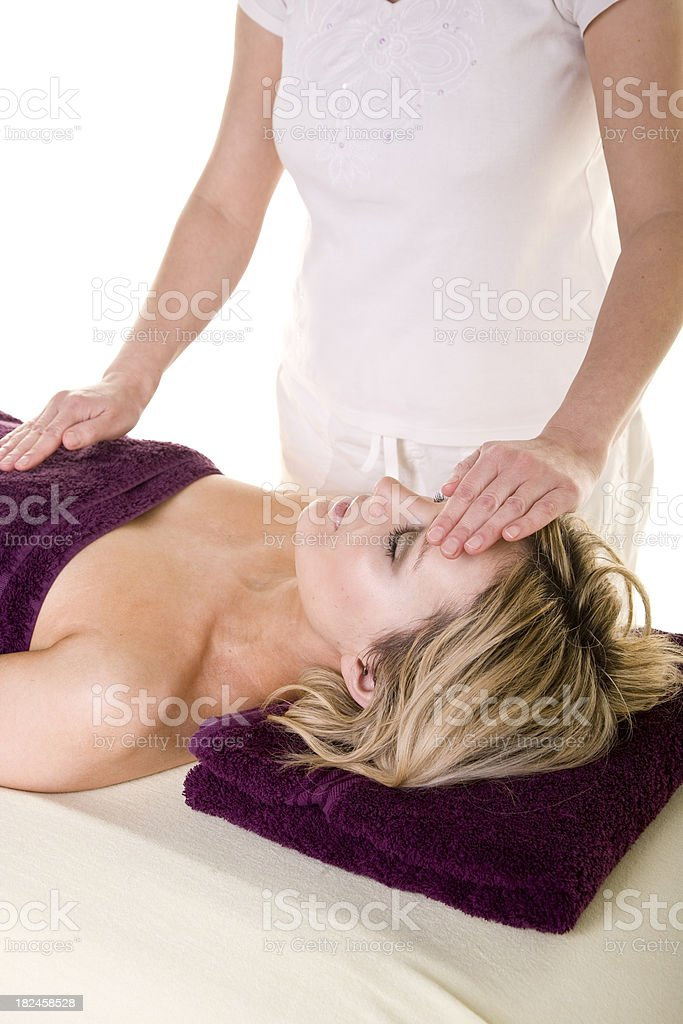 Attractive Young woman lying down having reiki treatment royalty-free stock photo