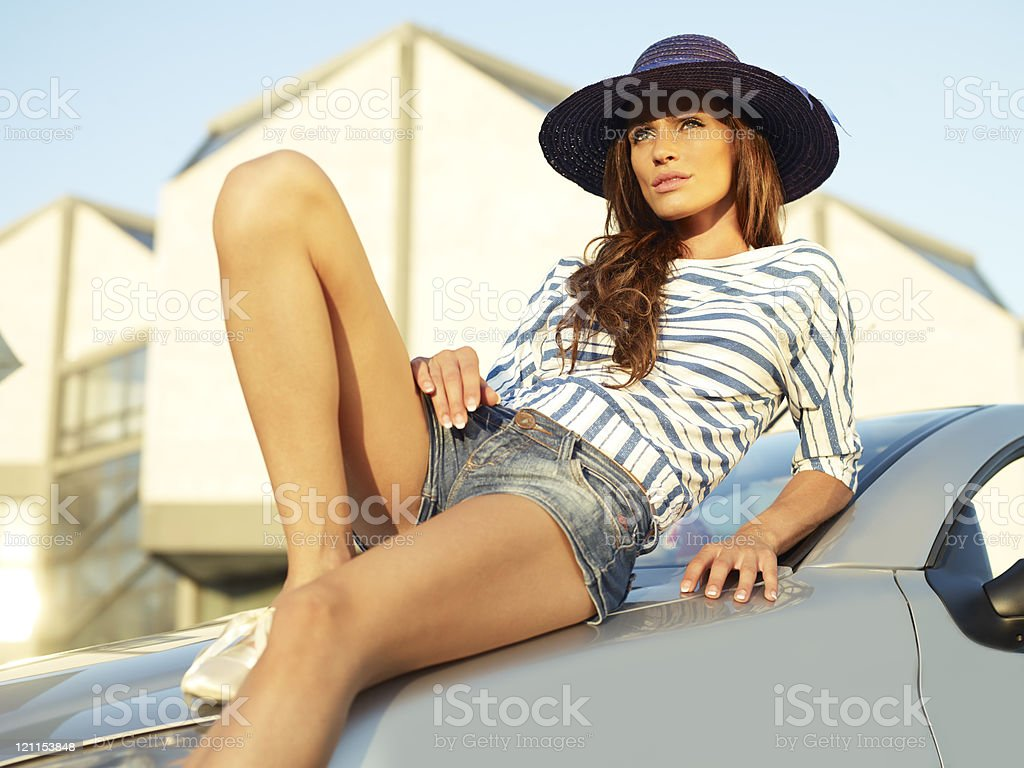 attractive young woman lying on the car royalty-free stock photo