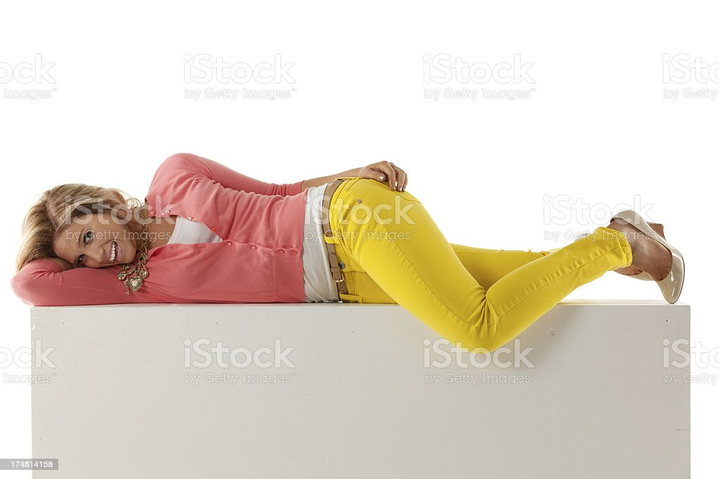 Attractive young woman lying on the ledge of a wall royalty-free stock photo