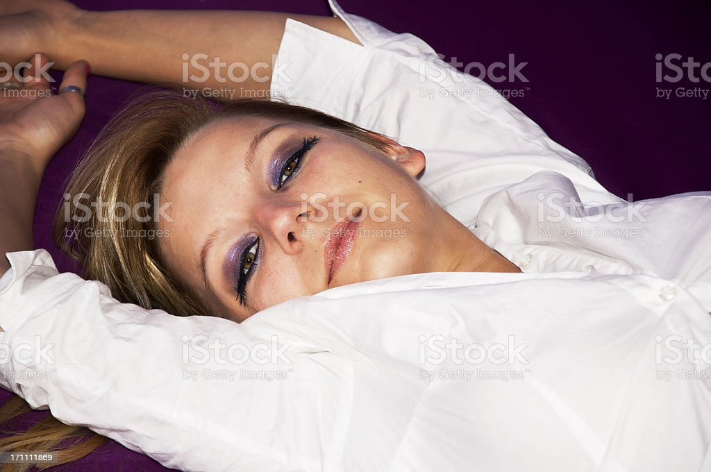 Attractive young woman lying on violett stock photo