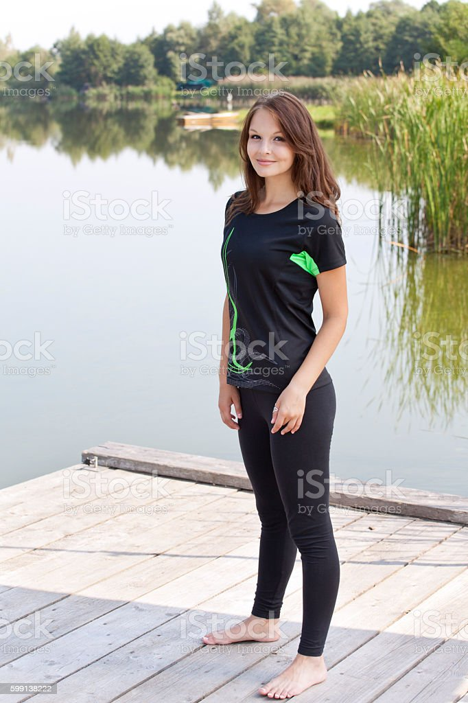 Attractive young woman near pond stock photo