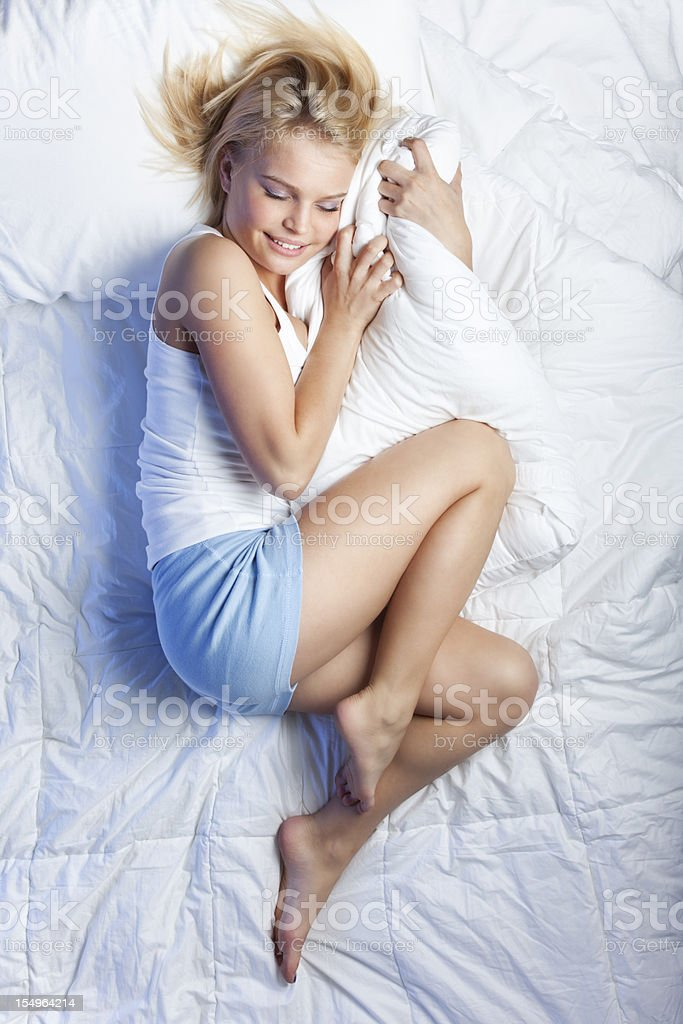 Attractive Young Woman on Bed Hugging Pillow stock photo