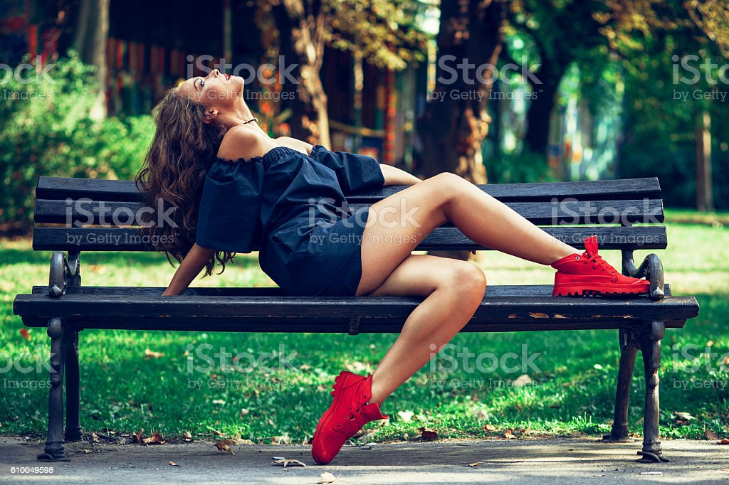 Attractive young woman posing on a bench in the park stock photo