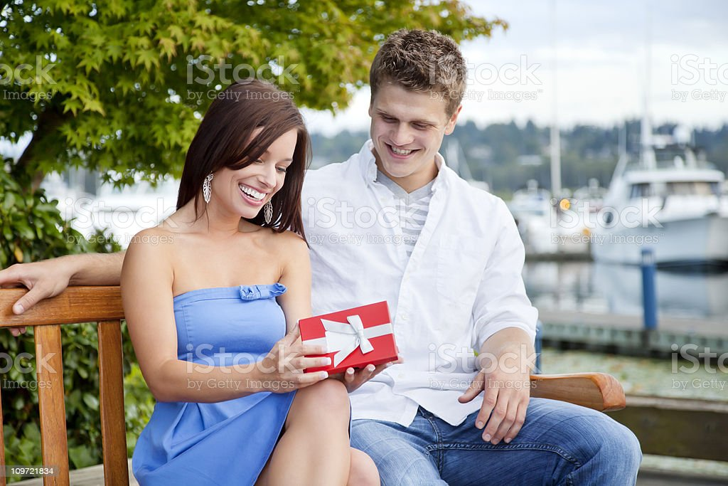 Attractive Young Woman Receiving Gift from Boyfriend royalty-free stock photo