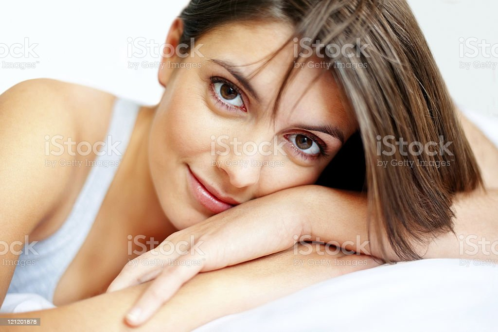 Attractive young woman relaxing in bed stock photo