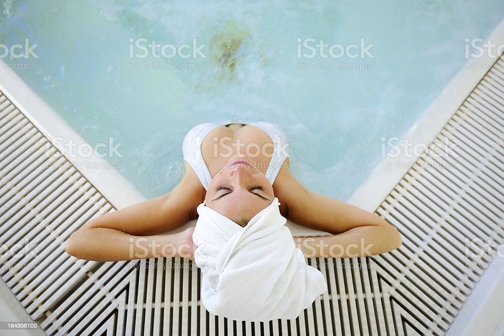Attractive young woman relaxing in the swimming pool. royalty-free stock photo