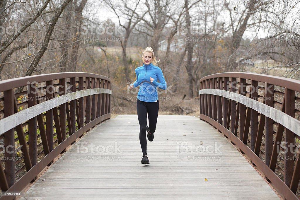 Attractive, young, woman running across bridge stock photo