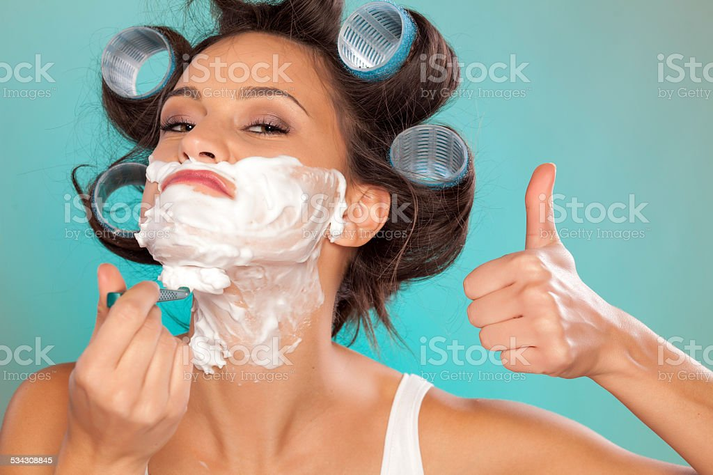 Attractive young woman shaving her face and showing thumb up stock photo