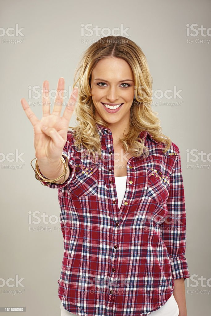 Attractive young woman showing four fingers royalty-free stock photo