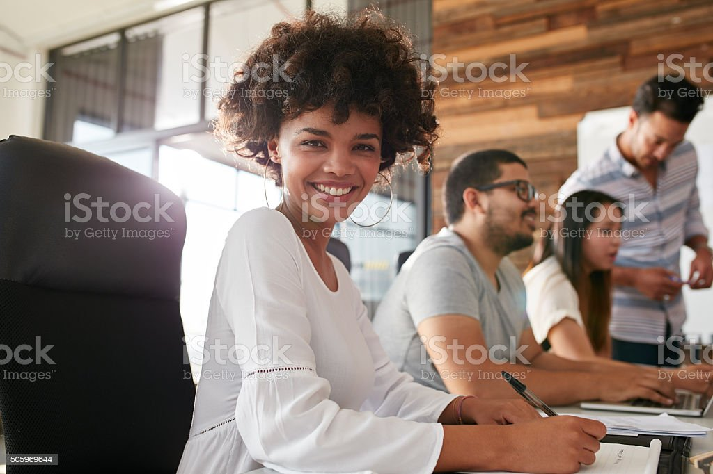 Attractive young woman sitting at conference room stock photo