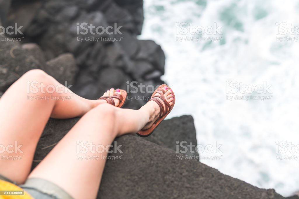 Attractive young woman sitting on outcropping of Hawaii beach watching the ocean stock photo