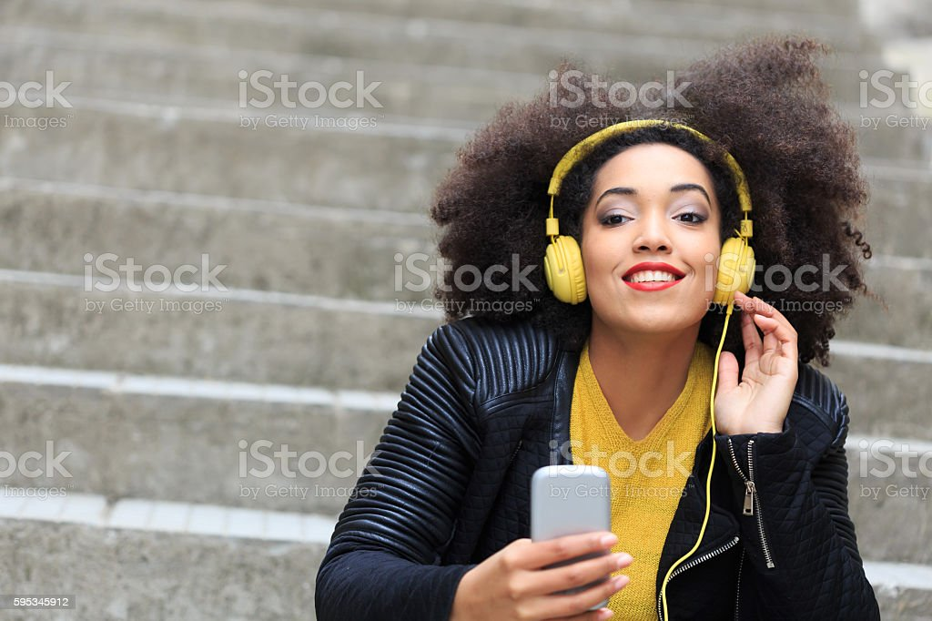 Attractive young woman sitting on stairs and listening music stock photo
