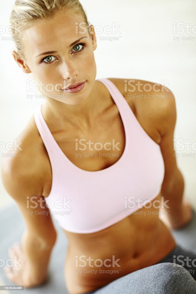 Attractive young woman sitting on yoga mat royalty-free stock photo