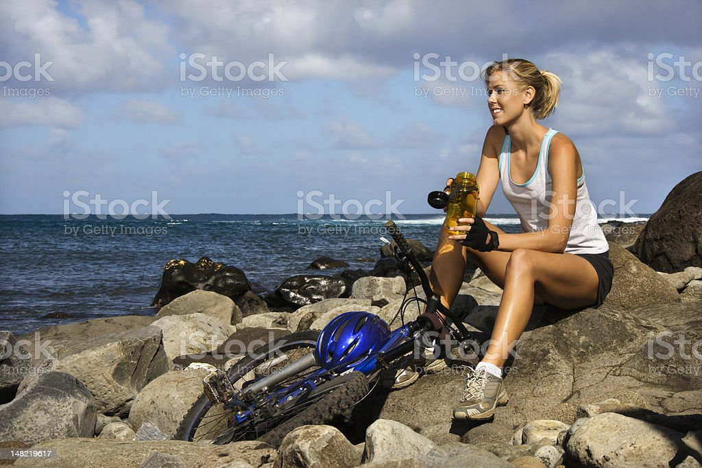 Attractive Young Woman Sitting With Bicycle on Rocky Beach royalty-free stock photo