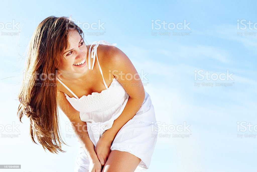 Attractive young woman smiling in white sundress against copy space royalty-free stock photo