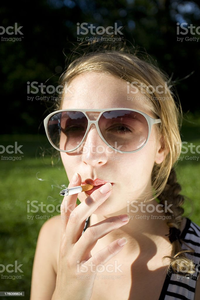 Attractive Young Woman Smoking a cigarette with Sunglasses royalty-free stock photo