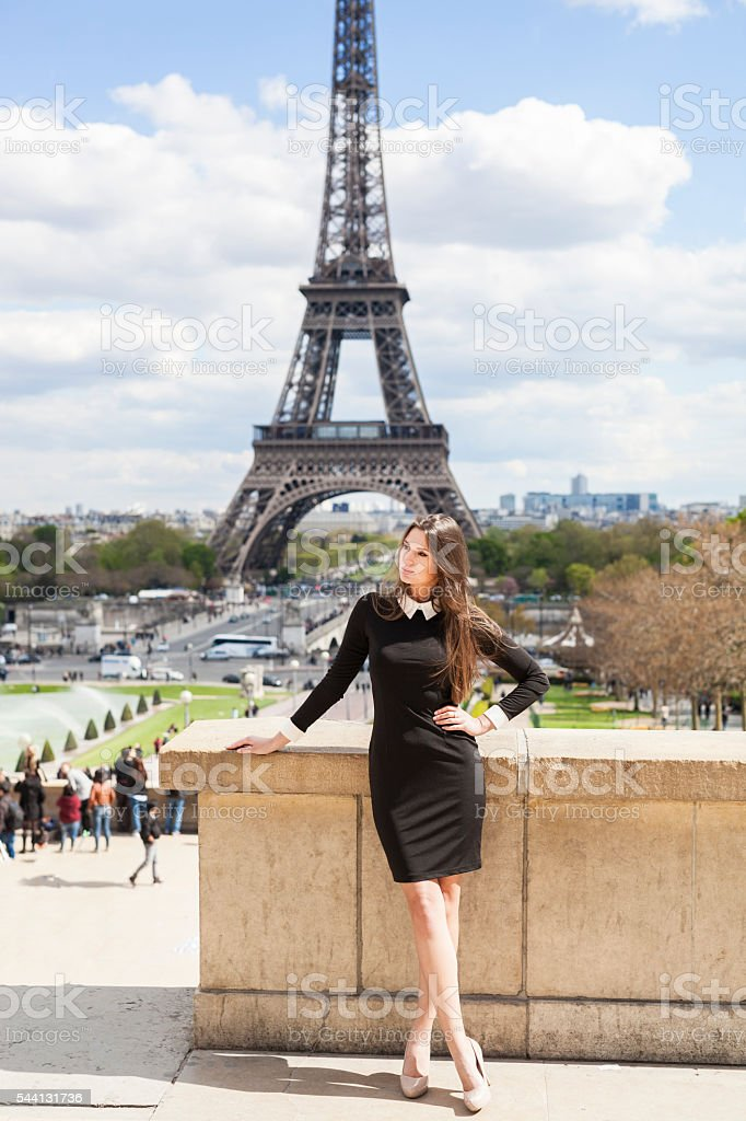Attractive Young Woman Standing At Eiffel Tower in Summertime stock photo