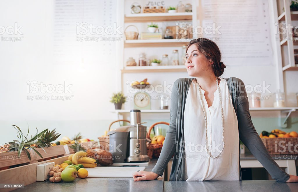 Attractive young woman standing behind the counter stock photo