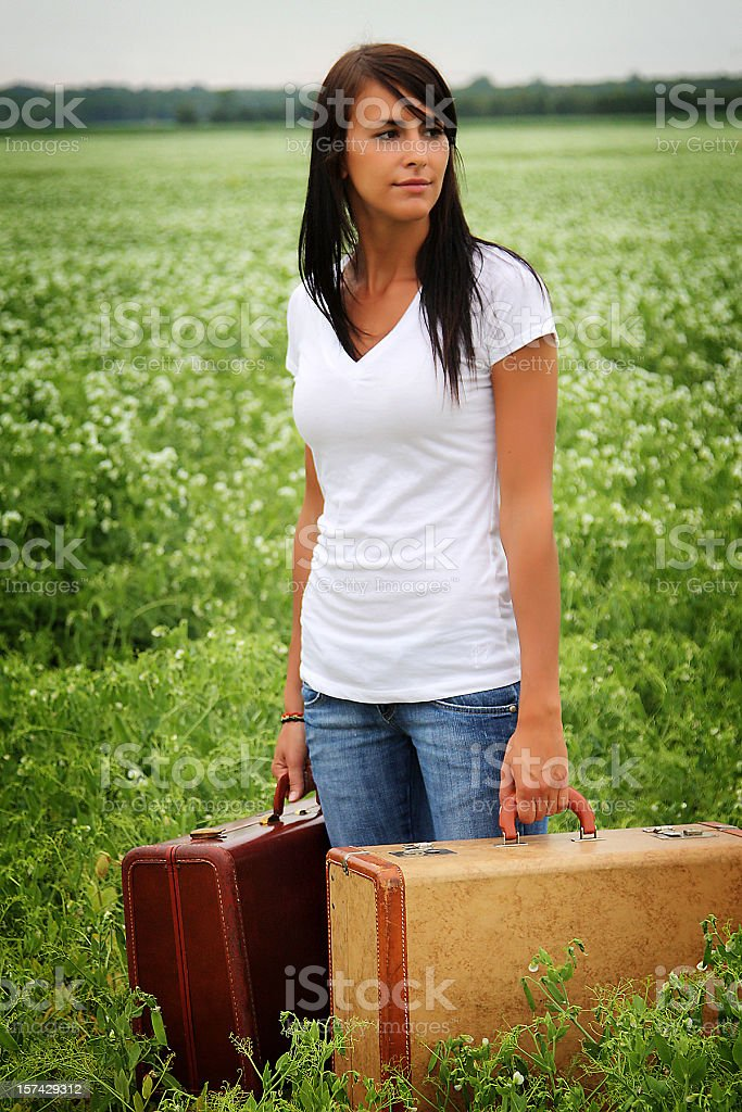 Attractive young woman standing in a field with two suitcases royalty-free stock photo