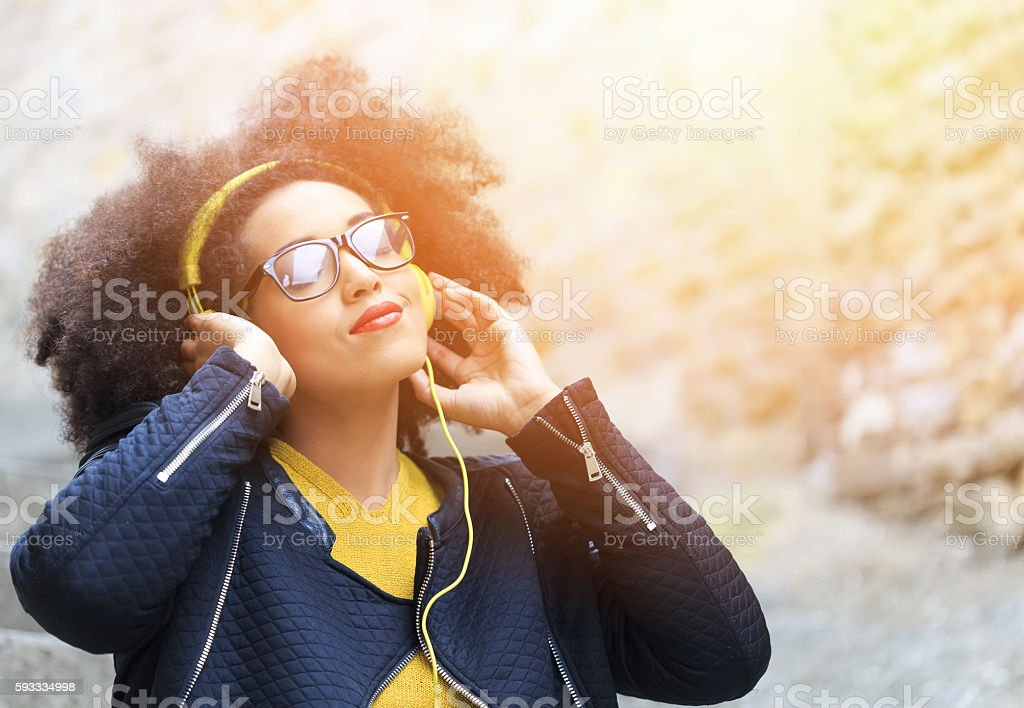 Attractive young woman standing on street and listening music stock photo