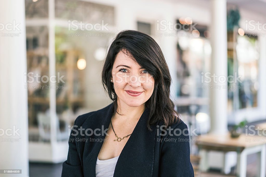Attractive young woman standing outside shop stock photo