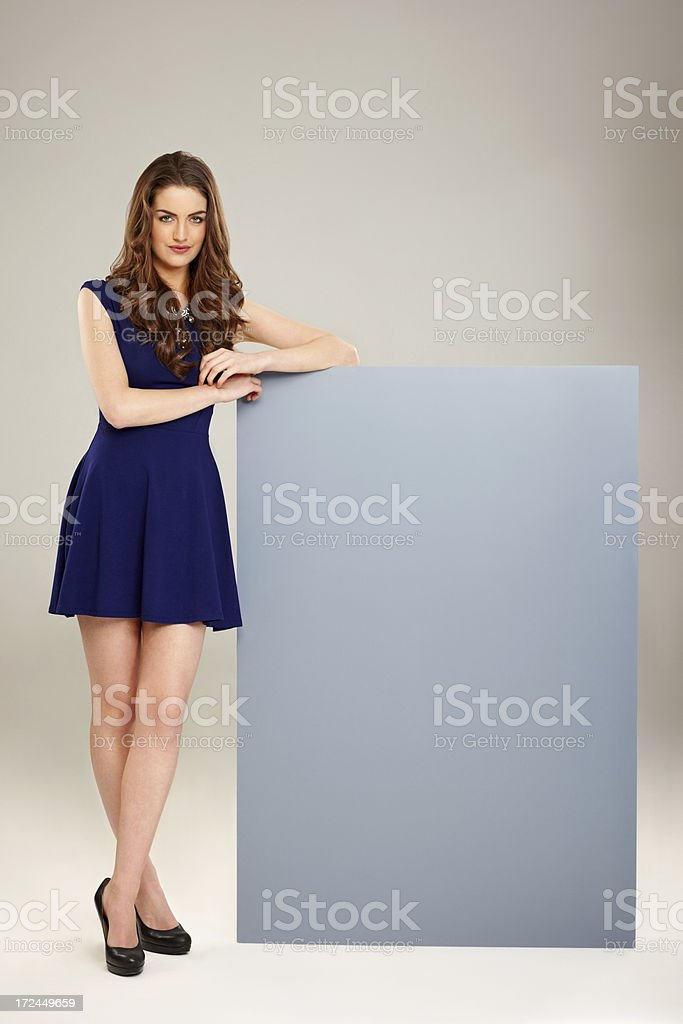 Attractive young woman standing with a blank signboard stock photo