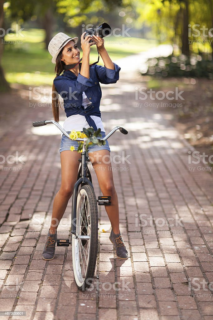 attractive young woman taking pictures on her bike stock photo