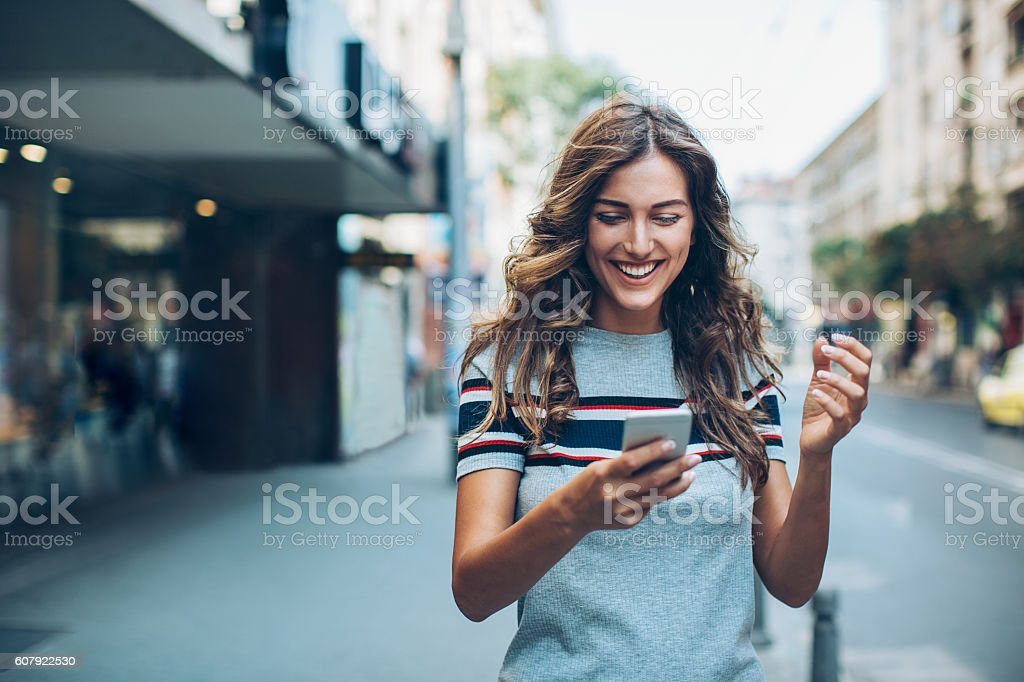Attractive young woman texting on the street stock photo