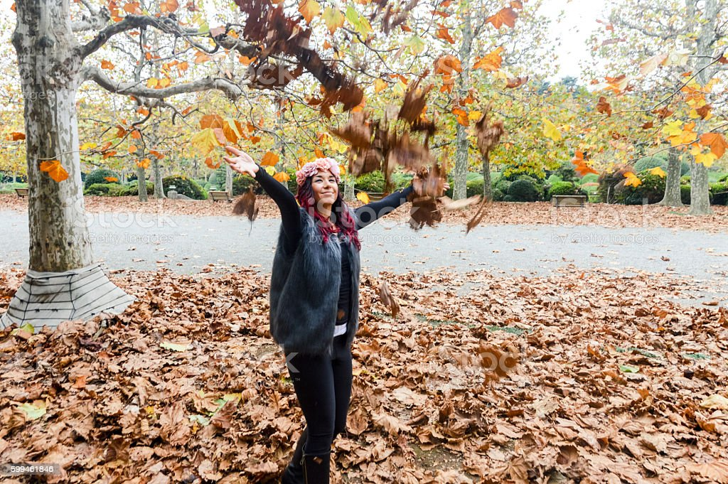 Attractive young woman throwing autumn leaves in the air stock photo