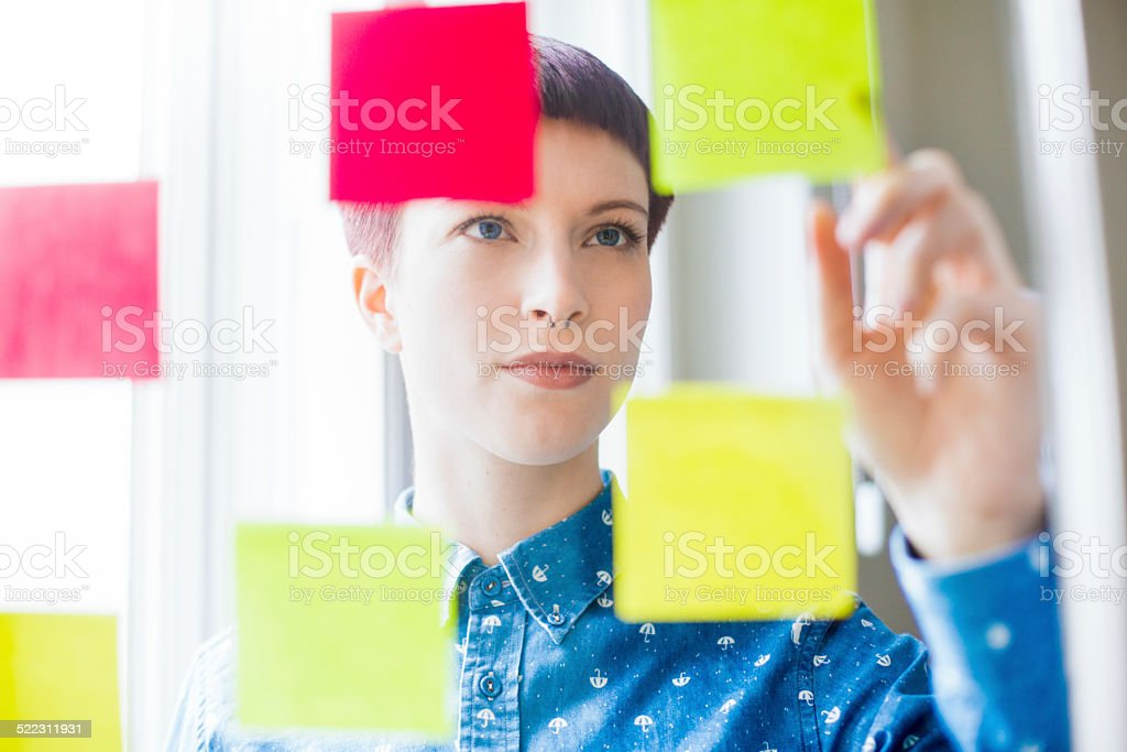 Attractive young woman viewing post-it notes stock photo