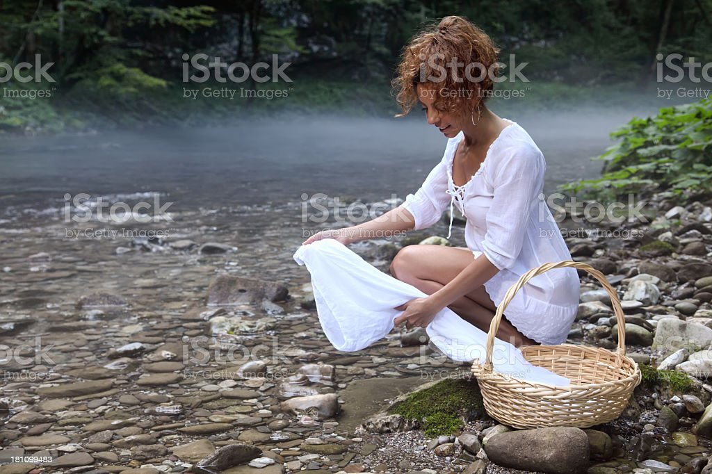 Attractive young woman washes clothes royalty-free stock photo