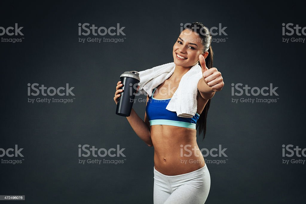 Attractive young woman with a protein shake holding thumbs up stock photo