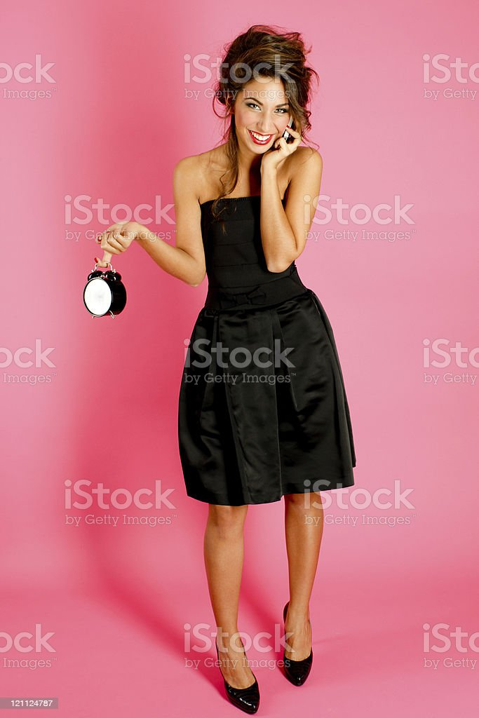 Attractive Young Woman with alarm clock and mobile phone stock photo