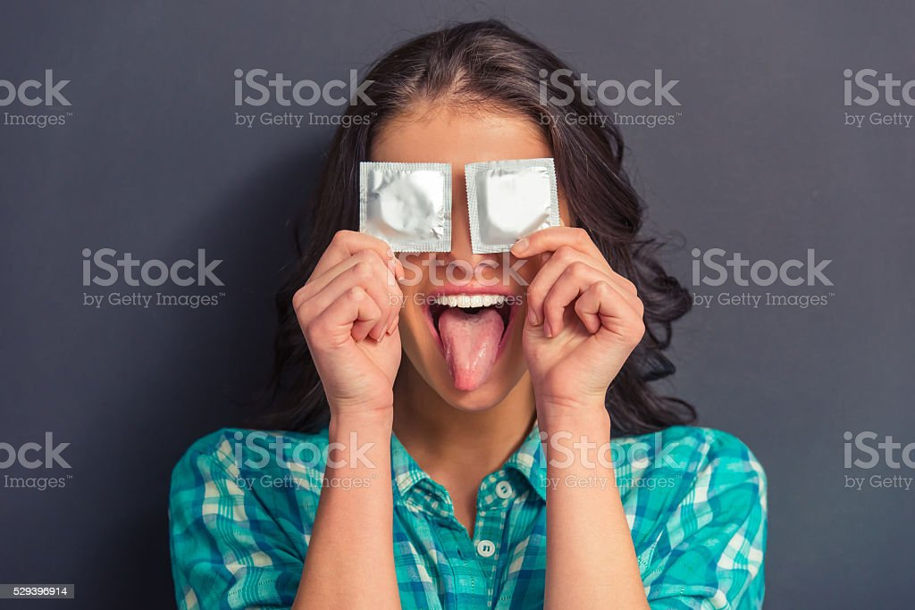 Attractive young woman with condom stock photo