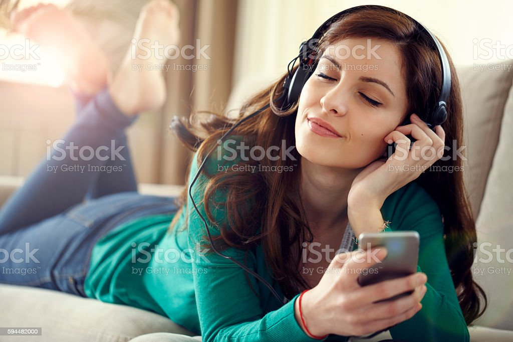 Attractive young woman with headphones listens music on smart ph stock photo