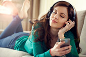 Attractive young woman with headphones listens music on smart ph