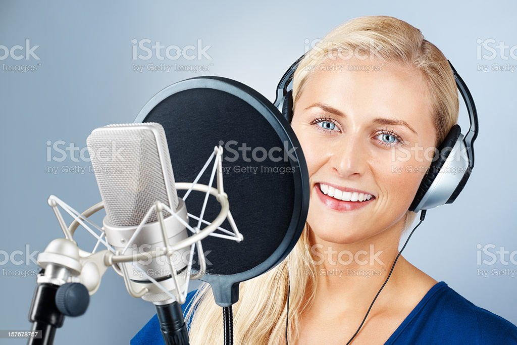 Attractive young woman with microphone and smiling stock photo