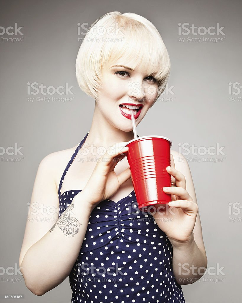 Attractive Young Woman With Polka Dot Dress and Beverage royalty-free stock photo