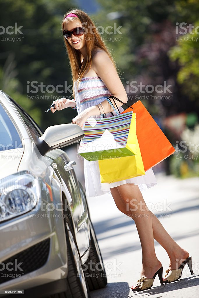 Attractive young woman with shopping bags entering car royalty-free stock photo