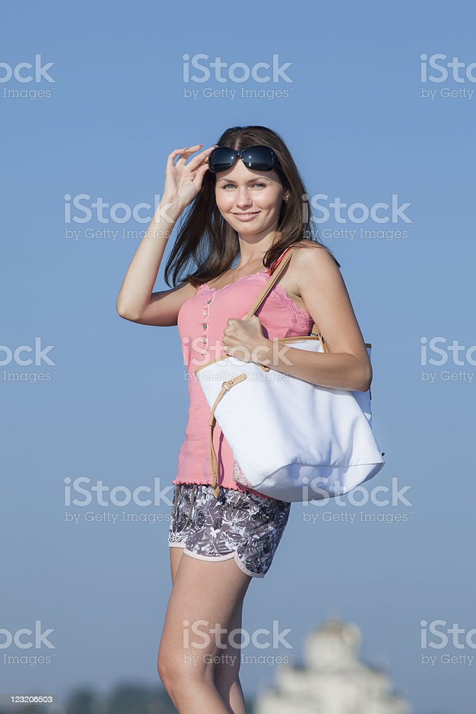 Attractive young woman with white bag looking at camera stock photo