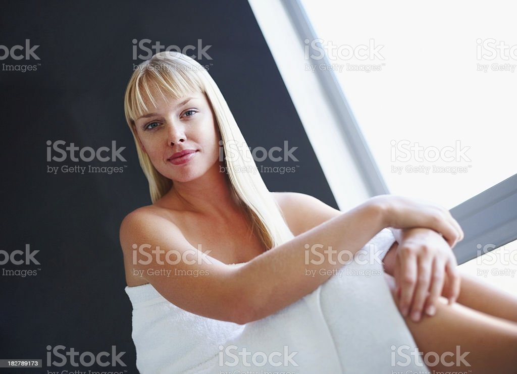 Attractive young woman wrapped in towel and smiling royalty-free stock photo