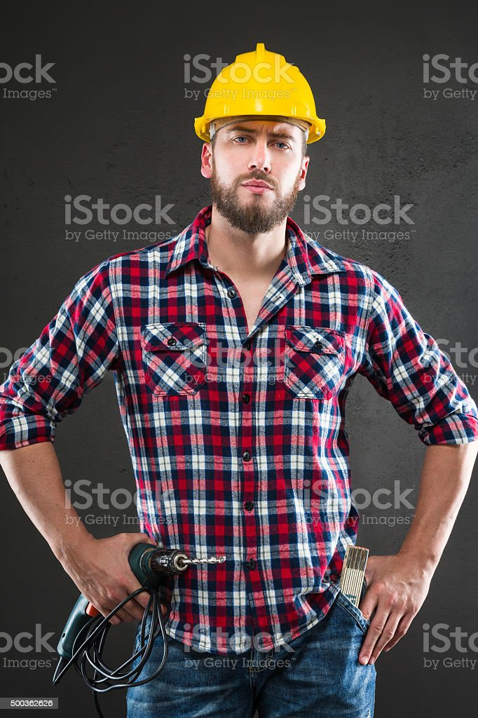 Attractive young workman with drill stock photo