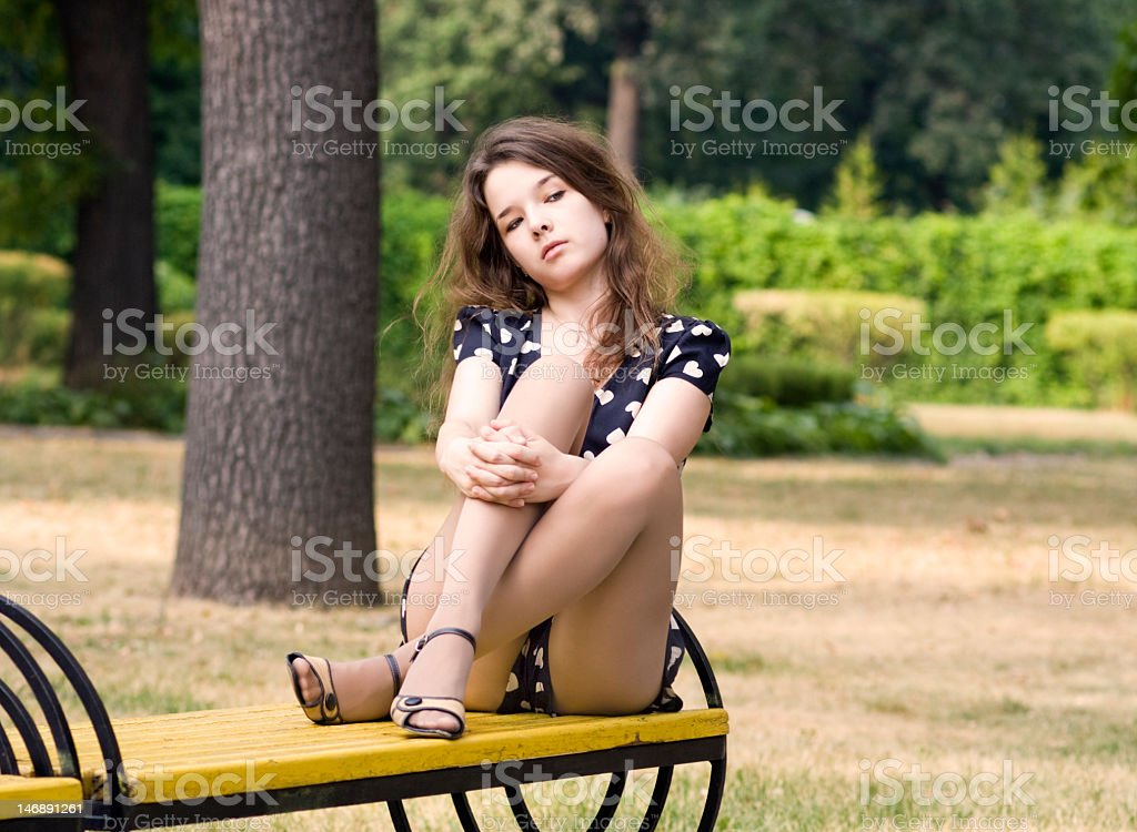 Attractiver  young woman crossed her legs on park bench stock photo