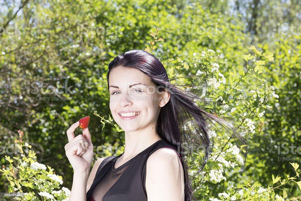 Attraktives Maedchen mit Erdbeere im Wald stock photo