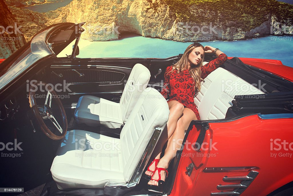 Attrractive blonde woman in red cabriolet royalty-free stock photo